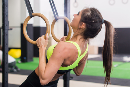 Athlete fit woman exercising in gym pulling up on gymnastic rings side view.