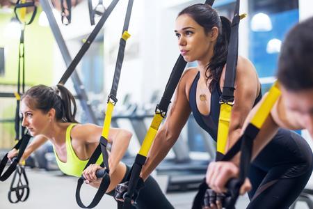 Mujer del atleta que hace pectorales con las correas de la aptitud del trx en el gimnasio Deporte sano de la forma de vida del entrenamiento del concepto. Foto de archivo - 90495933