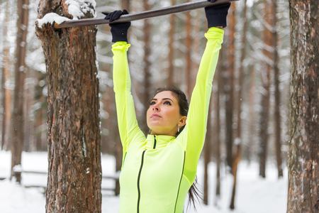 Fit woman athlete performing pull ups in a bar. Winter street outdoor training workout.