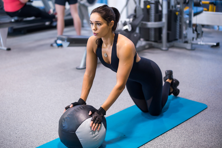 Fit woman exercising with medicine ball workout out arms Exercise training triceps and biceps doing push ups Stock Photo