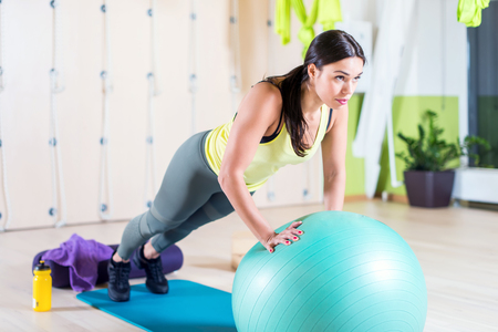 Fit woman doing push ups with medicine ball workout out arms Exercise training triceps and pectorals muscles Stock Photo