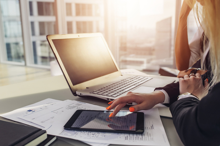 Close-up view of office desk: laptop, notebooks, papers, tablet computer at modern penthouse. Stock Photo