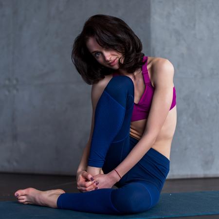 Pretty brunette model in sportswear posing sitting on floor barefoot in studio looking at camera