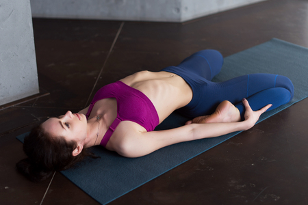 Pretty Caucasian girl wearing sports bra and leggings doing stretching yoga exercise lying in reclining hero pose on mat in studio Stock Photo