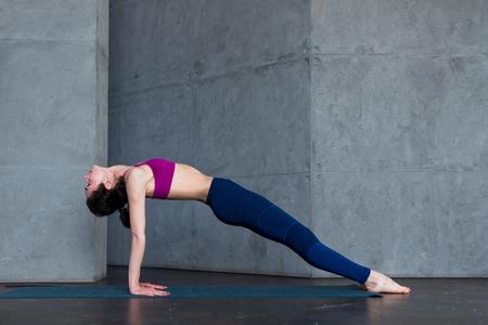 Pretty thin woman in sports bra and leggings doing yoga upward facing plank pose, purvottanasana, working out indoors Stock Photo