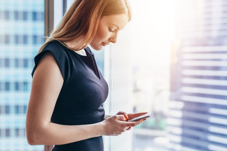Pretty smilingwoman using smartphone standing in office Stockfoto