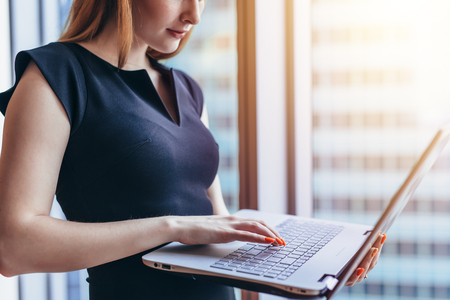 Close-up view of female worker holding laptop writing email in office building Stock Photo
