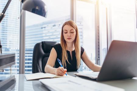 Naczelna kobieta siedzi przy biurku, robiąc notatki w notesie, pisząc piórem i używając komputera w nowoczesnym biurowcu