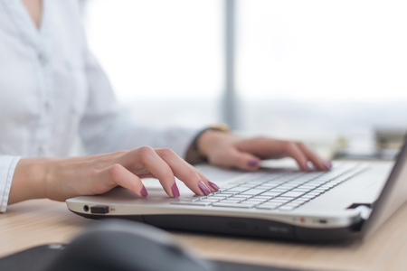 Working with laptop woman writing a blog. Female hands on the keyboard. Stock Photo