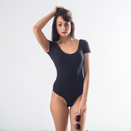 Cute brunette female model posing, wearing black one piece underwear suit, touching her hair 스톡 콘텐츠