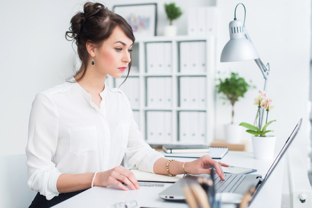 Attractive businesswoman working at office using pc, searching and studying business ideas on a laptop screen -line.