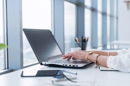 Copywriter femenino en su lugar de trabajo, hogar, escribiendo el nuevo texto usando la conexión a internet de la computadora portátil y de Wi-Fi por la mañana. Foto de archivo