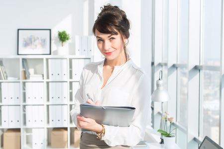 Attractive ambitious businesswoman standing in modern office, holding paper folder, looking at camera, smiling