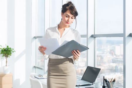 Beautiful, serious consultant wearing glasses and a formal office suit, holding her work stationary, looking at camera.
