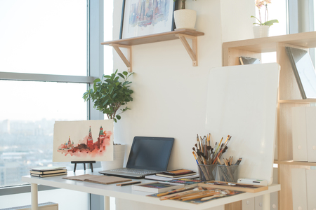 Painter workplace in order side view. Designer desk with drawing equipment. Home studio for artist