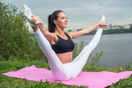Woman holding legs apart doing exercises aerobics warming up with gymnastics for flexibility leg stretching workout outdoors. Archivio Fotografico