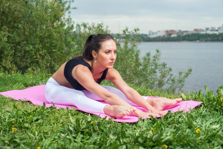 Fitness woman stretching back, hamstring leg muscles Seated forward bend.