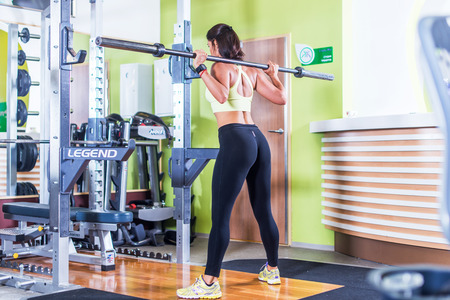 Fit woman doing squat with barbell in the gym. Imagens