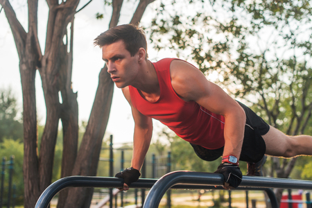 Fit young man doing push ups on horizontal bar outdoors Stock Photo
