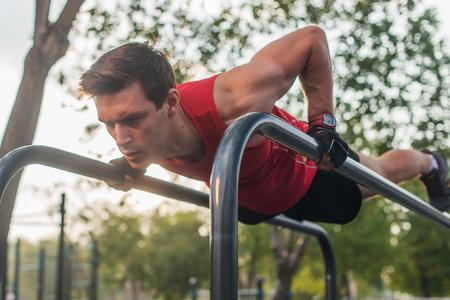 hombre joven con forma haciendo flexiones en la barra horizontal al aire libre Foto de archivo