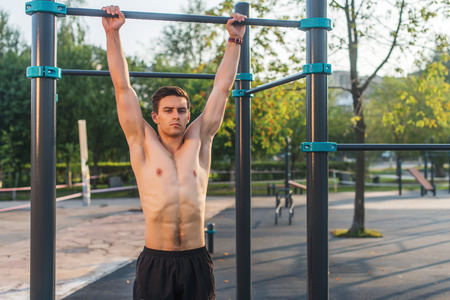 Fitnes man hanging on wall bars. Core cross training working out abs muscles