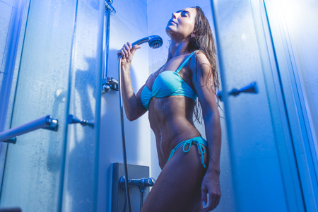 Cropped image of slim young womans body standing behind misted glass door a shower unit in blue light wearing white underwear