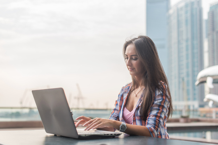 Young woman using laptop sitting with a cup of coffee.