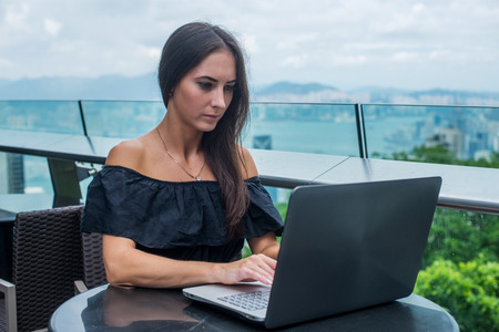 Young female freelancer dressed in black working on a project laptop computer while sitting at rooftop cafe terrace