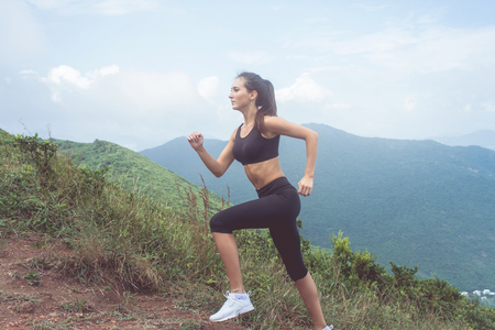 Side view of female athlete training, running outdoors in green mountains. Young woman wearing black sportswear working out in summer Stock Photo