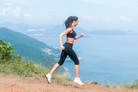 Cross-country female runner trail running on mountain path in summer. Woman wearing black sportswear exercising outdoors in wild nature