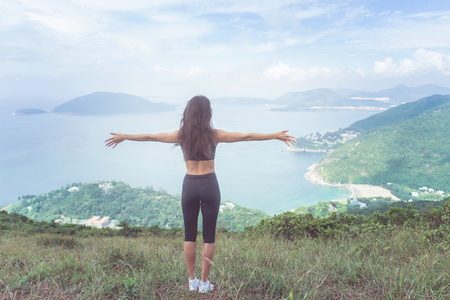Back view of fitness woman standing on green mountain with her arms outstretched looking at sea landscape expressing happiness and freedom Stock Photo - 93049869