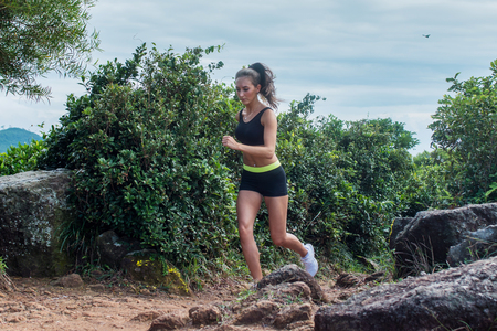 Fit athletic young woman running on dirty rocky path in mountains in summer.