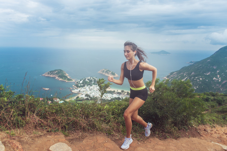 Young fit tanned woman trail running up the steps carved into the hillside with mountains, sea, islands and cloudy sky in background Stockfoto
