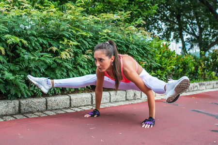 Sporty fit young woman doing handstand exercise in firefly posture. Female athlete working out in the park.
