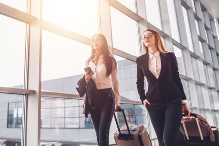 Two confident businesswomen carrying suitcases in airport