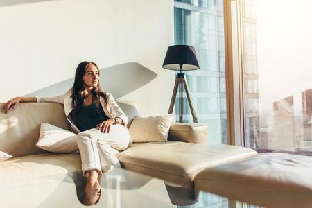 Porträt der erfolgreichen Geschäftsfrau den eleganten Gesellschaftsanzug tragend, der auf dem Ledersofa sich entspannt nach Arbeit zu Hause sitzt Standard-Bild
