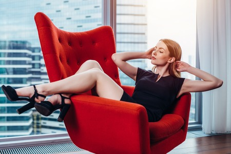 Elegant young woman relaxing on red stylish armchair in luxurious apartment