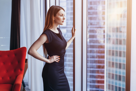 Well-off attractive woman thinking standing at the window admiring cityscape in her penthouse apartment Foto de archivo