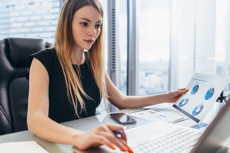 Weiblicher Direktor, der im Büro sitzt am Schreibtisch analysiert die Geschäftsstatistik hält Diagramme und Diagramme unter Verwendung des Laptops arbeitet
