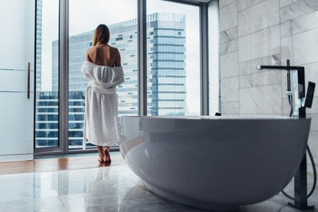 Back view of young woman wearing white bathrobe standing in bathroom looking out the window with bathtub in foreground Banque d'images