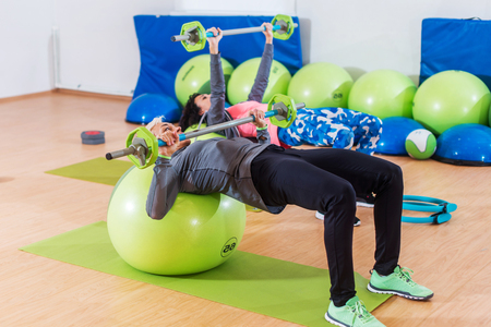 Girls in tracksuits lying on fitness balls doing barbell chest press in a gym. Two young women exercising indoors. Stock Photo
