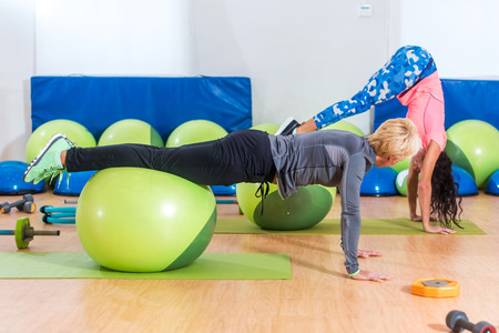 Slim young Caucasian women exercising doing stability ball roll outs with pull-in or handstand in a gym
