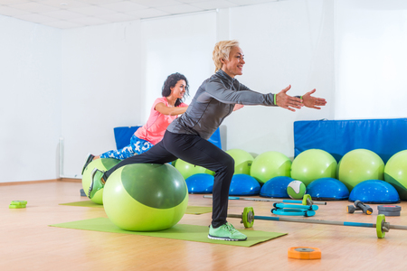 Active middle-aged woman working out with stability ball taking part in group fitness class Stock Photo