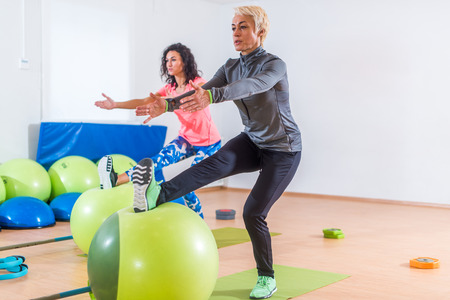 Group of active cheerful sporty women doing single leg squats with balance ball training indoors in gym Stock Photo