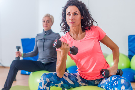 Smiling slim Caucasian women doing exercises with fitness balls and dumbbells looking at camera in a gym