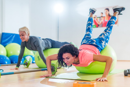 Two women exercising with stability balls doing push-ups in a gym class Stock Photo