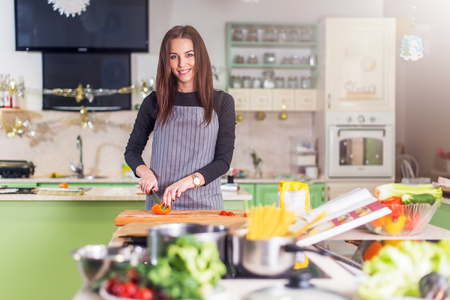 Pretty young Caucasian woman making pizza by recipe book, chopping vegetables on cutting board in her flat. Imagens