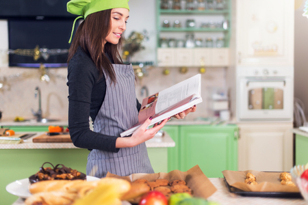 Young housewife trying to find a new recipe in cookbook while standing at table with food and ingredients