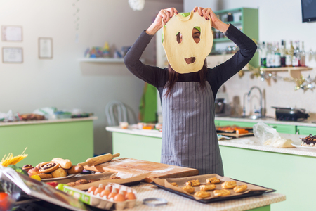 Young slim Caucasian woman baking in the kitchen having fun holding dough mask in front of her face