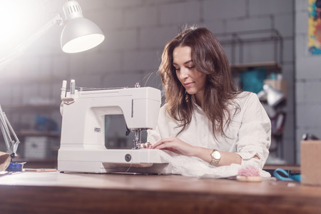 Aantrekkelijke blanke naaister werken stikken met naaimachine op haar werkplek in studio loft interieur